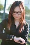 Geschäftsfrau, die Uhr überprüft Stockfotos