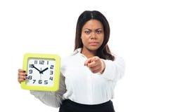 Geschäftsfrau, die Uhr hält und auf Kamera zeigt Stockfotos