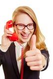 Geschäftsfrau, die um das Telefon hochhält ihren Daumen ersucht Stockfotografie