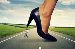 Geschäftsfrau, die unter großer Ferse steht stockbild