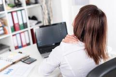 Geschäftsfrau, die unter Nackenschmerzen leidet lizenzfreies stockbild