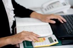 Geschäftsfrau, die unter Verwendung eines Taschenrechners arbeitet lizenzfreies stockbild