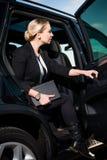 Geschäftsfrau, die vom Auto hinausgeht lizenzfreie stockfotografie