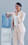 Geschäftsfrau, die von einem Wasserkühler trinkt Stockbild