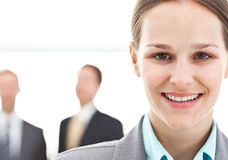 Geschäftsfrau, die vor zwei Geschäftsmännern aufwirft Stockbilder
