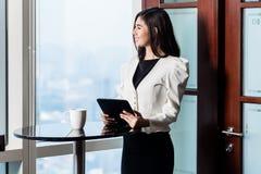 Geschäftsfrau, die am Wolkenkratzerfenster mit Skylineansicht steht lizenzfreie stockfotografie