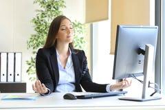 Geschäftsfrau, die Yoga im Büro tuend sich entspannt lizenzfreie stockbilder