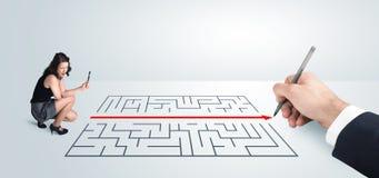 Geschäftsfrau, die Zeichnungslösung zur Hand nach Labyrinth sucht Lizenzfreie Stockfotografie