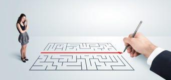 Geschäftsfrau, die Zeichnungslösung zur Hand nach Labyrinth sucht Stockfotos