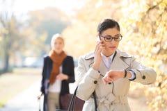 Geschäftsfrau, die Zeit während Kollege steht im Hintergrund am Park überprüft lizenzfreies stockfoto