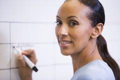 Geschäftsfrau, die zuhause auf löschbaren Vorstand schreibt lizenzfreies stockfoto