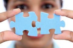 Geschäftsfrau, die zwei Puzzlestücken sich anschließt Lizenzfreies Stockbild