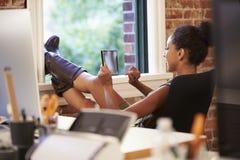 Geschäftsfrau With Digital Tablet, das im modernen Büro sich entspannt Lizenzfreies Stockfoto