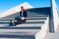 Geschäftsfrau draußen mit Laptop, weit Stockbilder