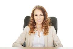 Geschäftsfrau durch einen Schreibtisch Lizenzfreie Stockfotografie