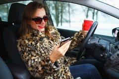 Geschäftsfrau in einem Pelzmantel mit den roten Lippen, die eine Textnachricht senden Stockbild