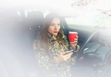 Geschäftsfrau in einem Pelzmantel mit den roten Lippen, die eine Textnachricht senden Lizenzfreie Stockfotografie