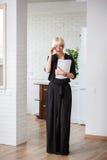 Geschäftsfrau in einem schwarzen Kleid mit einer Zeitschrift für die Aufzeichnungen Lizenzfreie Stockbilder