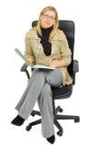 Geschäftsfrau in einem Stuhl mit Schreibarbeit Lizenzfreies Stockfoto