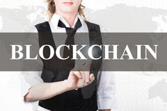 Geschäftsfrau in einer Jacke und in einer Bindung, die blockchain Knopf eines virtuellen Schirmes drücken Austausch und Produktio Stockbilder