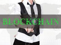 Geschäftsfrau in einer Jacke und in einer Bindung, die blockchain Knopf eines virtuellen Schirmes drücken Austausch und Produktio Lizenzfreie Stockfotografie