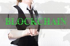 Geschäftsfrau in einer Jacke und in einer Bindung, die blockchain Knopf eines virtuellen Schirmes drücken Austausch und Produktio Lizenzfreie Stockfotos