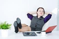 Geschäftsfrau entspannen sich mit den Fahrwerkbeinen auf der Tabelle stockfoto