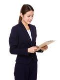 Geschäftsfrau gelesen auf Klemmbrett stockfoto