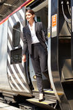 Geschäftsfrau Getting Off Train an der Plattform Lizenzfreie Stockfotos