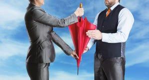 Geschäftsfrau gibt dem Geschäftsmann Regenschirm Stockfotos
