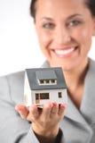 Geschäftsfrau hält Baumuster des Hauses an Lizenzfreie Stockfotos