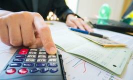 Geschäftsfrau-Handgriffstift und Gebrauchstaschenrechner auf Aussage oder Finanzbericht im Geschäftskonzept Stockbild
