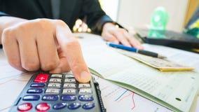 Geschäftsfrau-Handgriffstift und Gebrauchstaschenrechner auf Aussage oder Finanzbericht im Geschäftskonzept Stockfoto