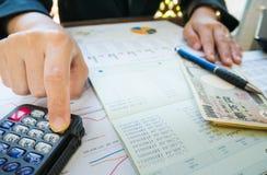 Geschäftsfrau-Handgriffstift und Gebrauchstaschenrechner auf Aussage oder Finanzbericht im Geschäftskonzept Stockfotos