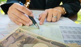 Geschäftsfrau-Handgriffstift und Punkt auf Aussage oder Finanzbericht und Japan-Geld im Geschäftskonzept Stockfotos