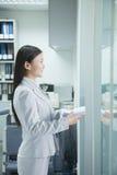 Geschäftsfrau-Handing Paper Through-Eingang Lizenzfreie Stockfotografie