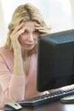 Geschäftsfrau-With Head In-Hände, die Computer-Monitor betrachten Lizenzfreie Stockfotos