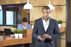 Geschäftsfrau-Holding Cellphone At-Aufnahme-Schreibtisch lizenzfreie stockbilder