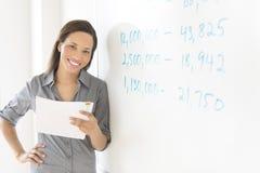 Geschäftsfrau Holding Document While, das sich herein auf Whiteboard von lehnt Lizenzfreies Stockfoto