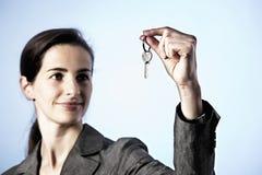 Geschäftsfrau-Holdingtaste zwischen Fingern Stockbild