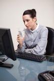 Geschäftsfrau an ihrem Schreibtisch mit einem Glas Wasser Stockfotografie