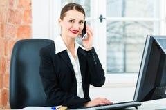 Geschäftsfrau im Büro, das auf dem Computer sitzt Stockfoto