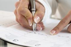 Geschäftsfrau im Büro, das eine Verabredung in ihrem Tagebuch, clos merkt lizenzfreies stockfoto