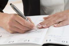 Geschäftsfrau im Büro, das eine Verabredung in ihrem Tagebuch merkt lizenzfreie stockfotografie