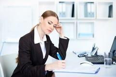 Geschäftsfrau im Büro, das etwas Schreibarbeit tut Stockbild