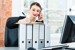 Geschäftsfrau im Büro macht Anmerkungen in einer Datei Stockfoto