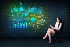 Geschäftsfrau im Büro mit Tablette in der Hand und High-Techem Diagramm Lizenzfreies Stockfoto