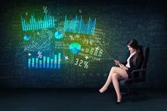 Geschäftsfrau im Büro mit Tablette in der Hand und High-Techem Diagramm Stockbild