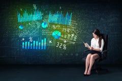 Geschäftsfrau im Büro mit Tablette in der Hand und High-Techem Diagramm Lizenzfreies Stockbild