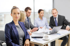 Geschäftsfrau im Büro mit Team auf der Rückseite Stockbild